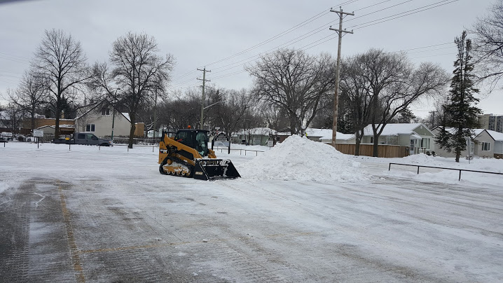 Skid Steer Plowing and Removing Snow From Parking Lot